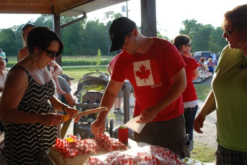 Allenford Improvement Association President Rodney Nickason and secretary Andrea Fisher serving Canada birthday cake.